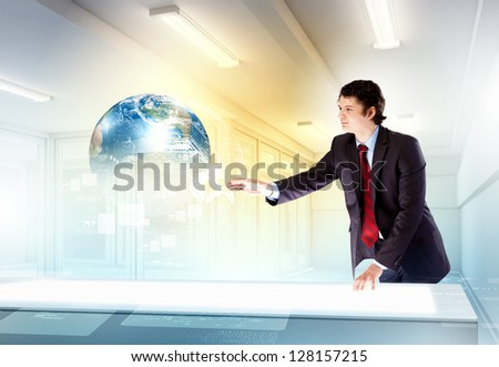Image of young businessman clicking icon on high-tech picture of globe - stock photo
