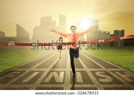 Image of young businessman defeat his rival in a race competition and crossing the finish line with numbers 2016 - stock photo