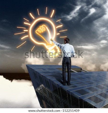 Image of young businessman drawing electric bulb - stock photo