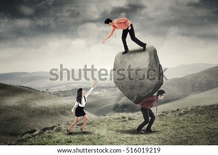Image of young businessman helping his colleague by hand while standing above the stone with his partner on the hill