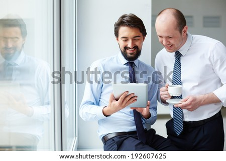 Image of young businessman holding touchpad while explaining idea to his colleague at meeting - stock photo