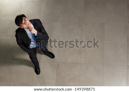 Image of young businessman in glasses looking thoughtfully. Top view - stock photo