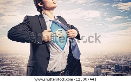 Image of young businessman in superhero suit with euro sign on chest - stock photo