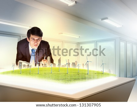 Image of young businessman looking at high-tech picture of windmills - stock photo