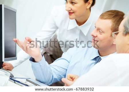 Image of young businessman pointing at computer monitor while making presentation - stock photo