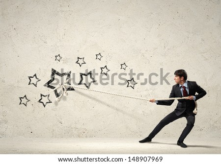 Image of young businessman pulling stars with rope - stock photo