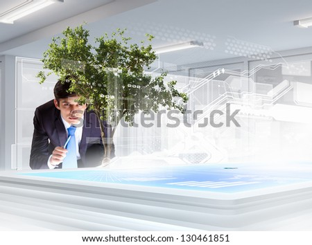 Image of young businessman touching icon of high-tech picture of environment concept - stock photo