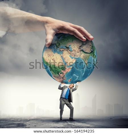 Image of young businessman under pressure of planet Earth. Elements of this image are furnished by NASA - stock photo