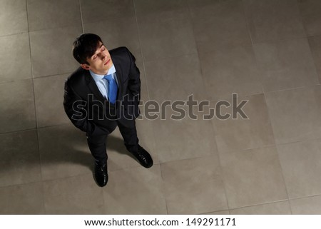 Image of young businessman with his eyes closed looking above. Top view - stock photo