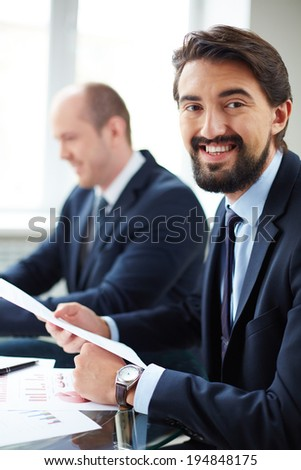 Image of young businessman working with papers on background of his colleague