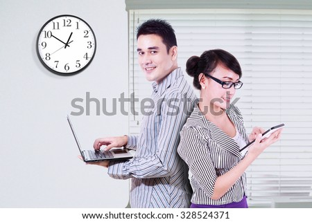 Image of young businesspeople standing in the office while using laptop computer and digital tablet - stock photo