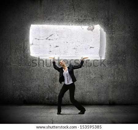 Image of young businesswoman holding burden above head - stock photo