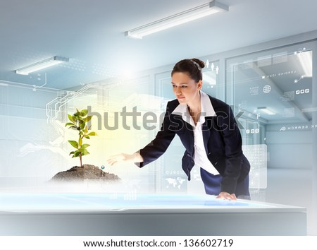 Image of young businesswoman holding cup standing against high-tech picture - stock photo