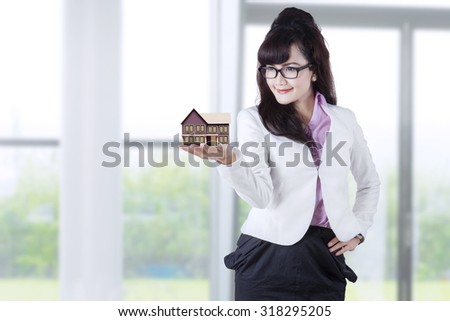 Image of young businesswoman holding house miniature at home. Real estate concept