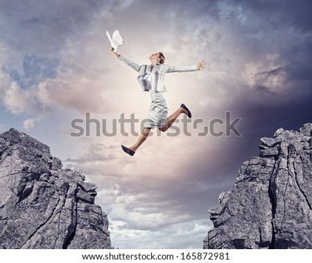 Image of young businesswoman jumping over gap - stock photo