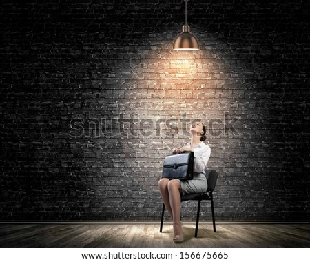 Image of young businesswoman sitting on chair under spot of light - stock photo