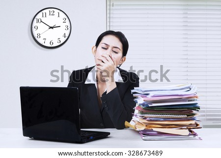 Image of young businesswoman yawning in the office while working with laptop and business documents - stock photo
