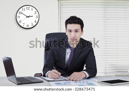 Image of young caucasian businessman working in the office with a clock on the wall and laptop on the table - stock photo