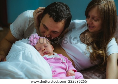 Image of young caucasian family indoor. Father, mother and cute little girl. Dad, mum and newborn baby in pink suit.