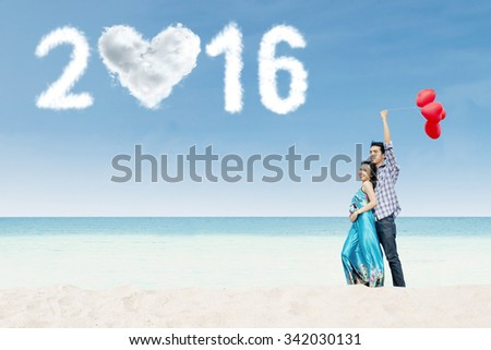 Image of young couple standing on the beach while holding balloons with clouds shaped numbers 2016 - stock photo