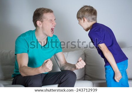 Image of young dad yelling at his son - stock photo