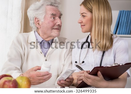 Image of young doctor examining male patient of nursing home - stock photo