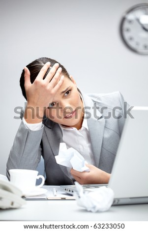 Image of young employer looking at laptop with anxiety - stock photo