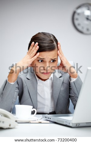 Image of young employer looking at laptop with troubled expression