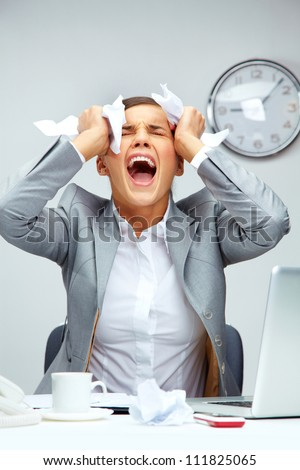 Image of young employer touching her head in frustration and crying at workplace - stock photo