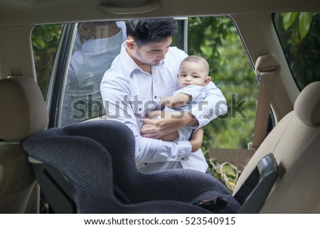 Image of young father holding his son while standing near car window with a car seat