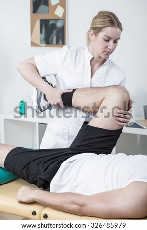 Image of young female physiotherapist working with male patient