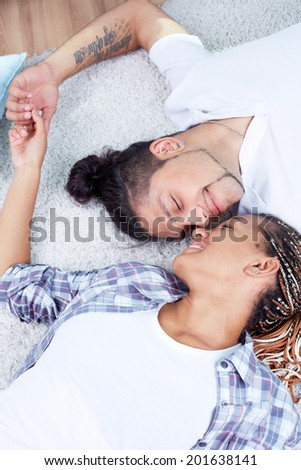 Image of young guy and his girlfriend lying on the floor and holding by hands - stock photo