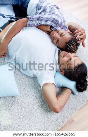 Image of young guy and his girlfriend relaxing at home - stock photo