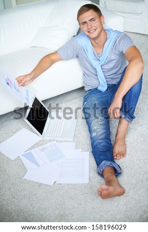 Image of young guy in casual sitting on the floor and looking at camera with smile - stock photo