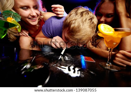 Image of young guy sniffing cocaine surrounded by two girls in night club - stock photo