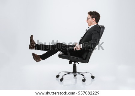 Image of young handsome businessman sitting on chair at studio. Isolated over white background. Look aside.