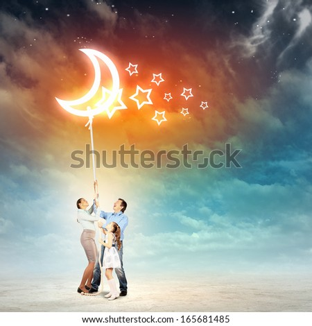 Image of young happy family pulling rope with a moon - stock photo