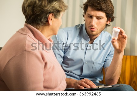 Image of young helpful man assisting elderly female - stock photo