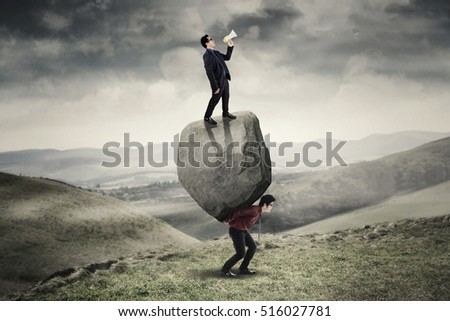 Image of young leader screaming with megaphone and standing on the stone while his employee lifting stone on the hill