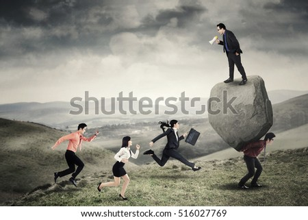 Image of young leader shouting at his employees with a megaphone while standing above the stone and his partner on the hill