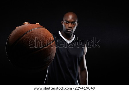 Image of young man holding a basketball against black background with copy space. Fit basketball player with focus on ball. - stock photo