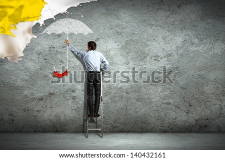 Image of young man holding illustrated umbrella - stock photo