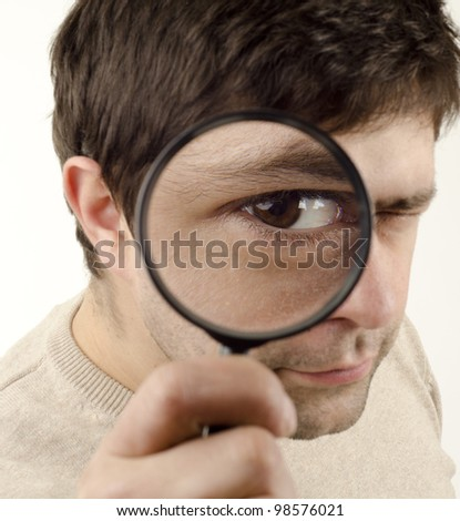 Image of young man looking through a magnifying glass - stock photo