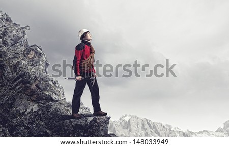 Image of young man mountaineer standing atop of rock - stock photo