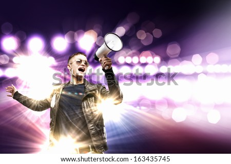 Image of young man rock musician screaming in megaphone - stock photo