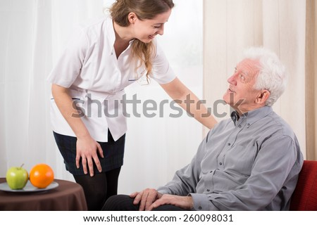 Image of young nurse caring about elder man - stock photo