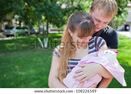 Image of young parents holding the hands of his first child - a girl on a sunny summer day. Almaty. - stock photo