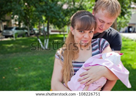 Image of young parents holding the hands of his first child - a girl on a sunny summer day. Almaty.
