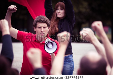 Image of young rebellious man with megaphone during street protest - stock photo