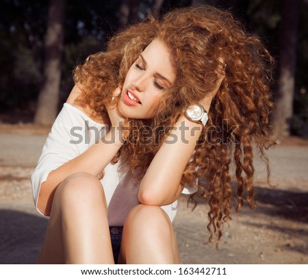 Image of young red haired woman with curls . Beautiful Brunette Girl. Healthy Long red hair . beauty model female.  stylish haircut. Glossy smooth curly Hair. Sensual look Urban- street shot.   - stock photo